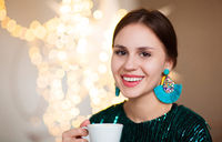 Young woman enjoying smell of hot beverage