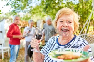 Fröhliche Seniorin mit einem Glas Rotwein