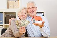 Glückliche Senioren mit Dollar und Haus