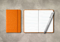 Orange closed and open lined notebooks with a pen on concrete background