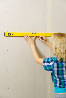 DIY blond young attractive woman using spirit level to work out measurements on plasterboard wall.