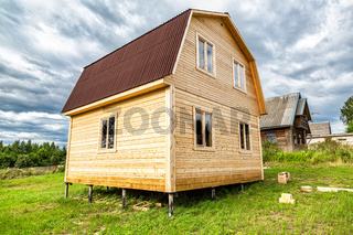 New small wooden house under construction at the village