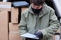 Paketbote mit Mundschutz prüft Lieferungen vor Laderaum