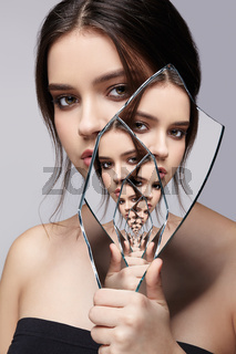 Female with mirror shard in hand posing on gray background. Multiple reflections in mirror splinter.