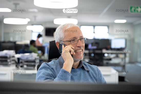 Senior businessman talking on smartphone while sitting on his desk at modern office
