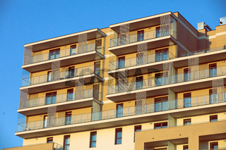 A high multi-family apartment block against a blue sky.