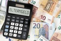 word ELTERNGELD on display of pocket calculator against Euro currency banknotes