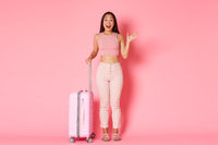 Travelling, holidays and vacation concept. Cheerful glamour asian girl in summer clothes, tourist waving hand in hello gesture as someone meeting her airport, holding suitcase over pink background
