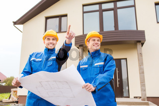 smiling builders with blueprint pointing finger