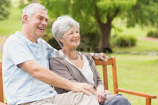 Side view of senior couple sitting on bench at park