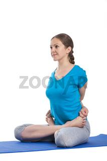 Yoga - young beautiful woman  yoga instructor doing bound lotus pose (Baddha Padmasana) exercise isolated on white background