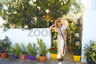 Stylish woman standing in green garden