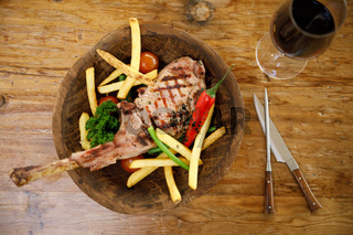 Tomahawk steak with fries, vegetables and a glass of red wine