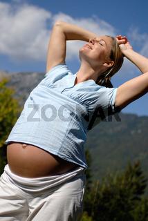 Schwangere Frau steht in der Sonne