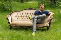 Mid aged man relaxes sitting at comfortable home sofa in garden outdoors. High quality photo