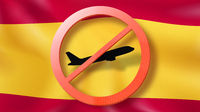 Warning sign with crossed out plane on the background of Spanish flag.