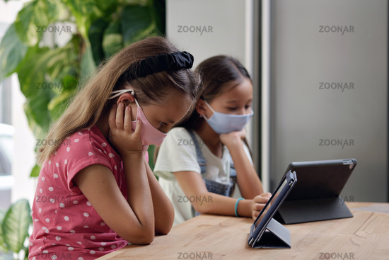 Asian and Caucasian girls in face masks using tablet devices sit indoors