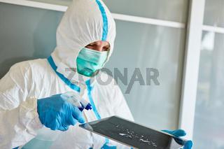 Reinigungskraft bei Desinfektion von Touchscreen eines Tablet Computer