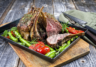 Barbecue rack of lamb neck with paprika and tomato offered as closeup on a metal tray