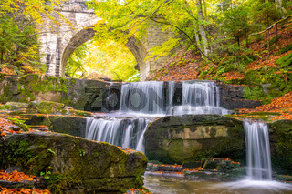Arch of a Stone Bridge in the Forest and River Waterfall