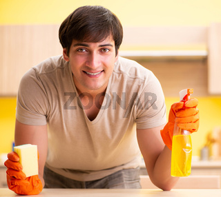 Single man cleaning kitchen at home