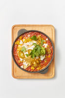 Shakshuka dish with pita bread in a pan on a wooden board.