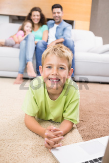 Smiling little boy using laptop on the rug with parents sitting sofa