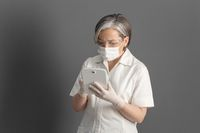 Female doctor works with digital tablet. Caucasian woman in protective mask and gloves stands against of gray wall on background and uses electronic gadget