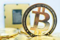 Closeup of physical bitcoin and computer cpu processor