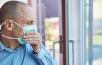 Senior als Covid-19 Patient mit Mundschutz beim Husten