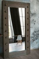 Mirror in a wooden frame with light bulbs around. In the reflection of the mirror is a white chair. Grey wallpaper. High quality photo