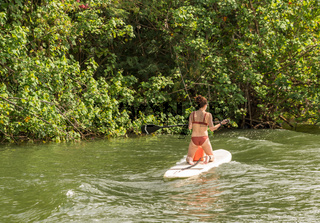 Rear view of woman on stand up paddleboard as waves from boat rock her board
