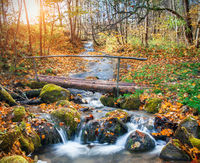 beautiful cascade waterfall  and wooden bridge in autumn forest
