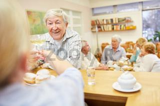 Alter Mann trinkt mit Betreuerin ein Glas Wein am Tresen im Seniorenheim