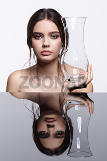 Girl holding in hand a glass vase. Beauty portrait of young woman at the mirror table.
