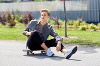 teenage boy sitting on skateboard on city street