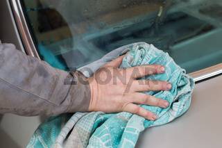 The hand is wiping the car with a rag.