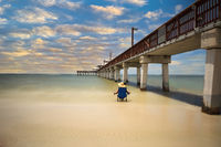 Sunset over Lone woman relaxing beside the Boardwalk of the Fort Myers Pier on Fort Myers Beach