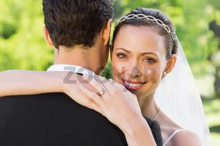 Beautiful bride embracing groom in garden