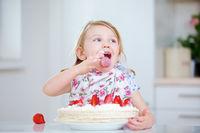 Kind leckt Sahne vom Finger beim Kuchen essen