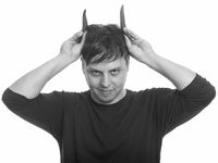 Studio shot of crazy man with peppers as horns