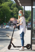 Casual caucasian teenager commuter waering protective face mask against spreading of corona virus with modern foldable urban electric scooter waiting for metro city bus. Urban mobility concept