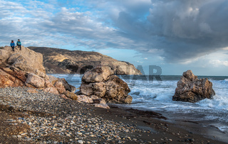 Women  sitting on a rock and enjoying the beautiful stormy seascape. Paphos Cyprus