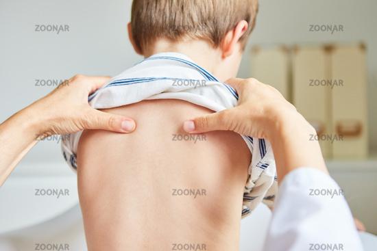 Osteopath macht Akupressur am Rücken von Kind