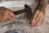 Silberschmied graviert eine Silberplatte mit Hammer und Nagel