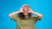 Funny pilot gesture African American girl looking positively at camera wearing olive t-shirt with hands as binoculars isolated on blue background. Beauty concept