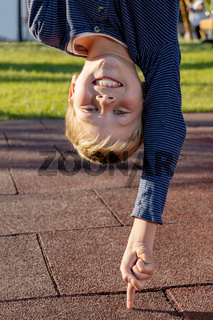 Young boy standing with one finger upside down