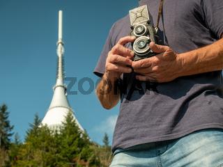 Pensioner using analog camera during trip in mountains