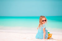 Little adorable girl playing on beach with ball