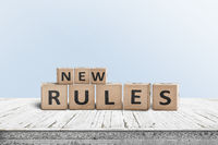 New rules sign made of wood on a desk
